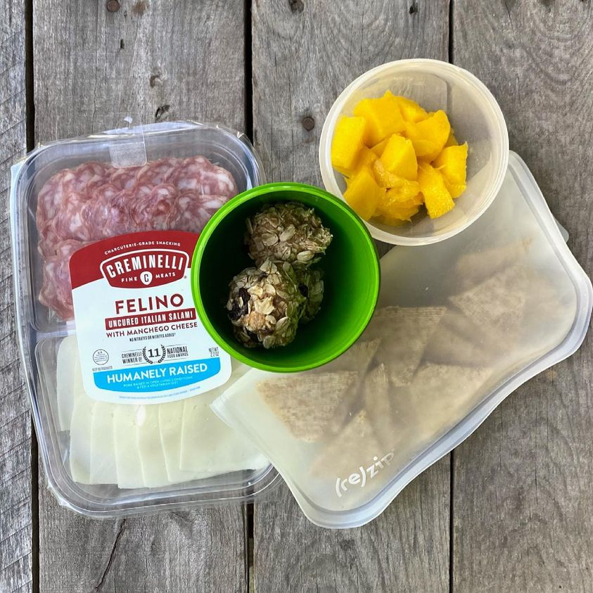 Packed school lunch that includes a charcuterie plate with salami and cheese, thin Triscuits, homemade Oatmeal Cookie Energy Bites, and mango.