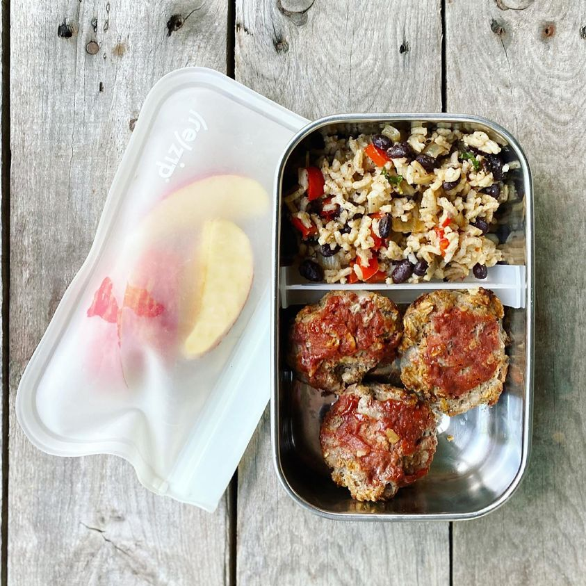 Packed school lunch that includes mini meatloaves with rice and beans, and apple slices.