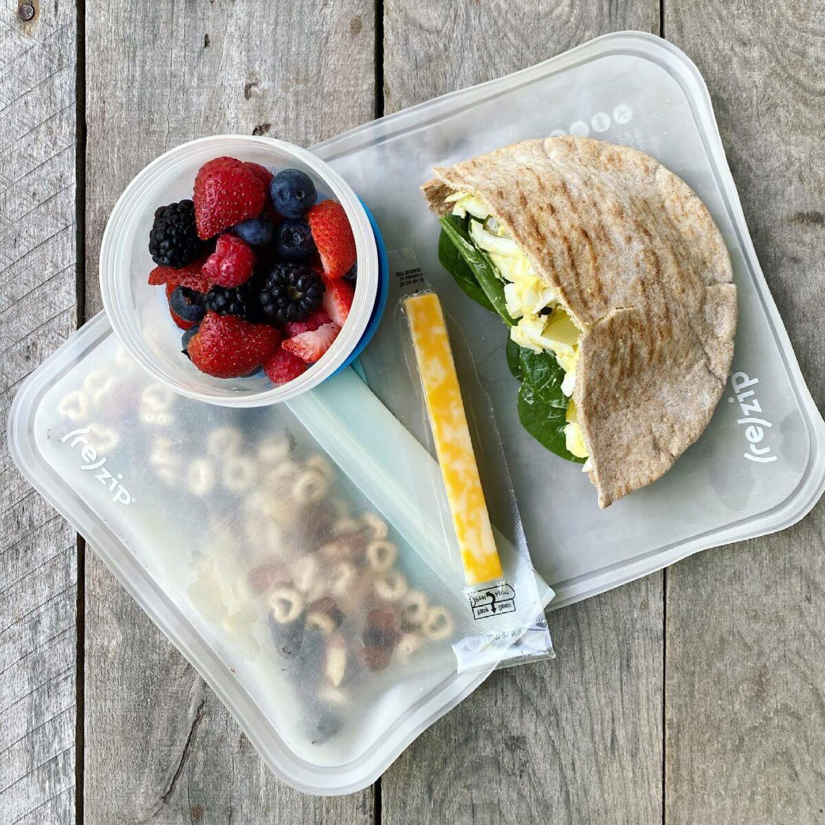Packed school lunch that includes an egg salad sandwich, cheese stick, mixed berries, and homemade trail mix.