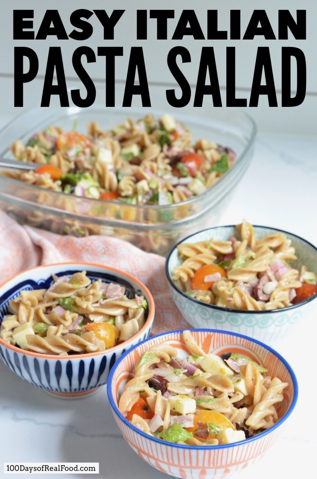 Four colorful bowls of homemade Italian pasta salad on the counter.