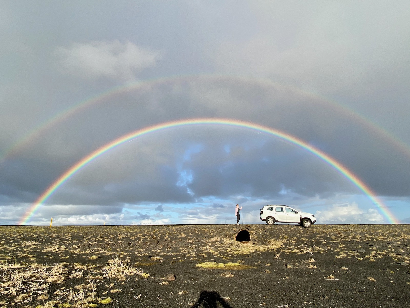 Double rainbow over an open field in Iceland.