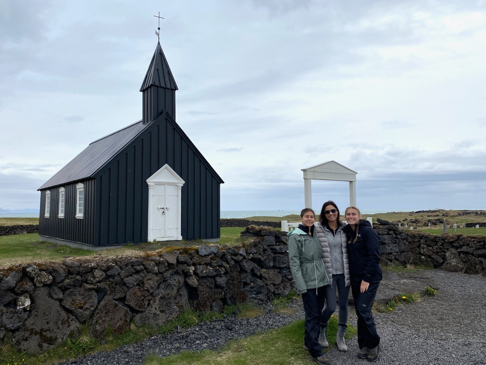 Mother and two daughters posing in front of a quaint little church in Iceland.