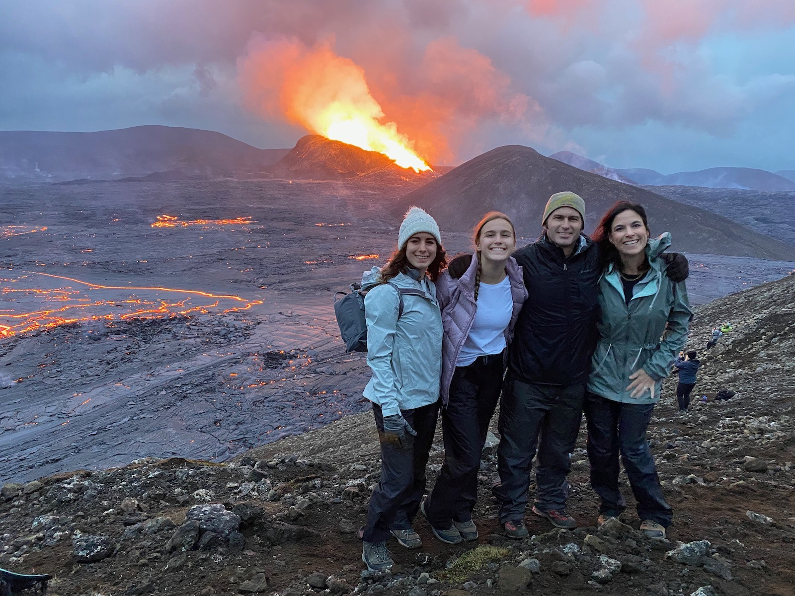 Family posing in front of erupting Fagradalsfjall Volcano.