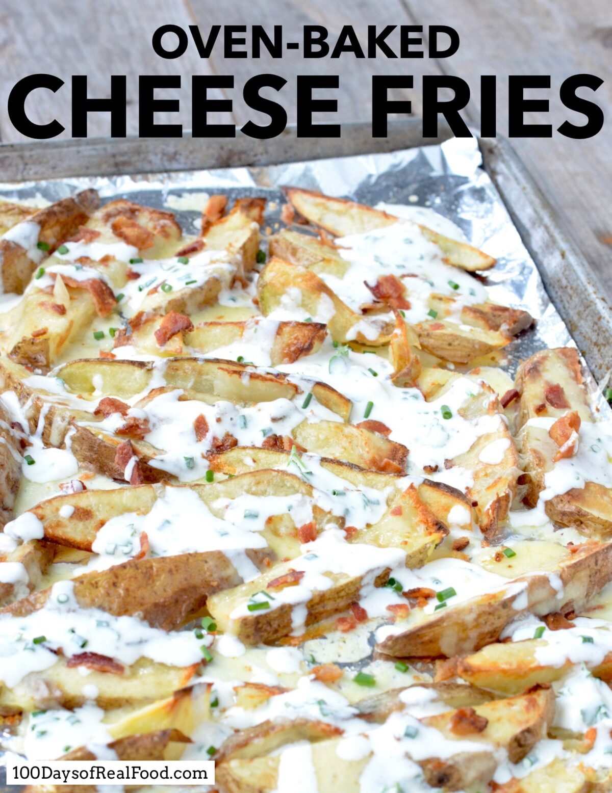 Sliced potatoes topped with cheese, bacon, and homemade ranch dressing on a baking sheet.