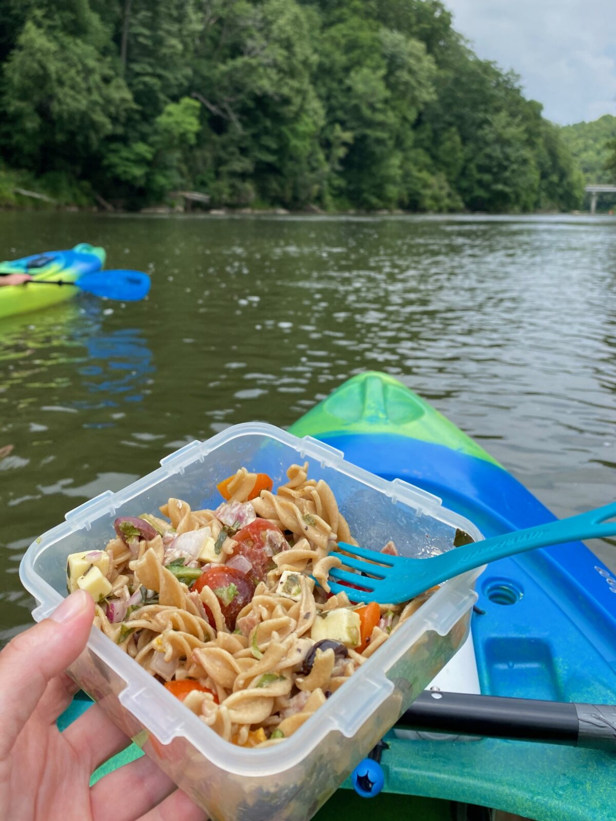 From a human perspective, sitting on a kayak on the water, holding a jar of pasta salad.